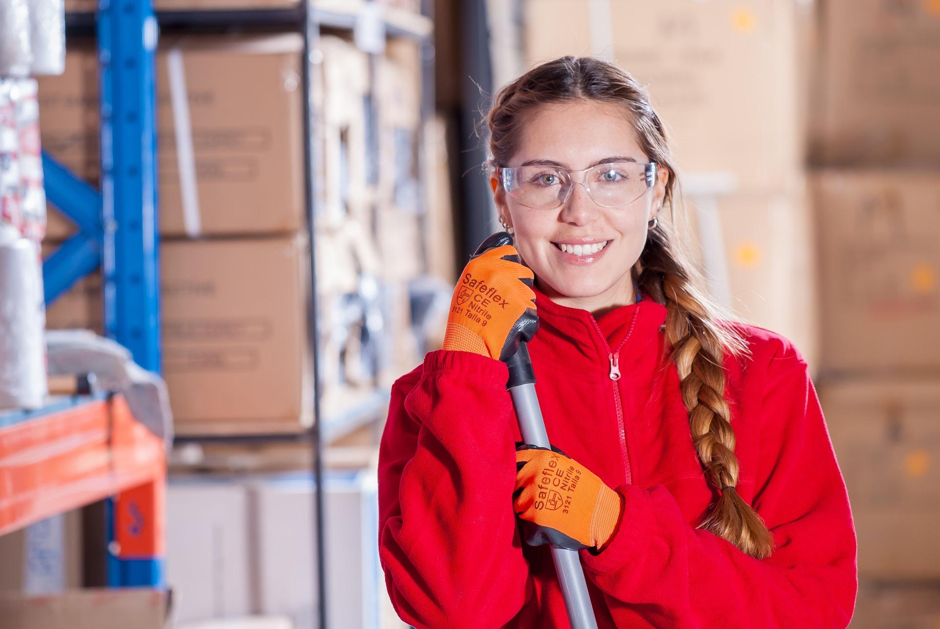 Gebäudereinigung und Unterhaltsreinigung. Reinigungsfrau posiert mit Besen. Wir reinigen Ihr Büro.